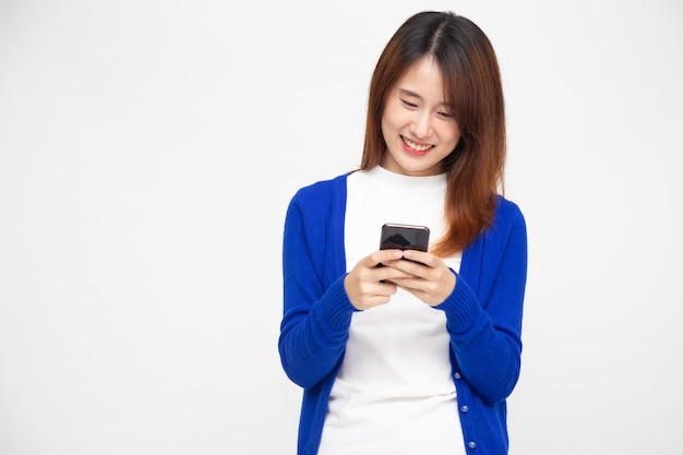 Aziatische vrouw die smartphoneon over witte muur gebruikt