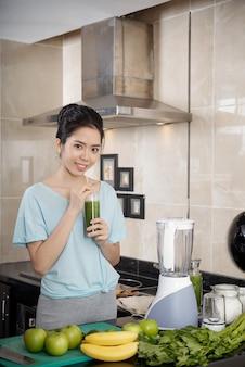 Aziatische vrouw die smoothie drinkt in de keuken