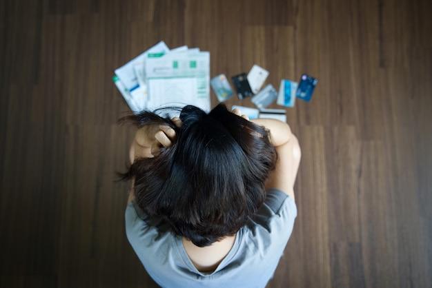 Aziatische vrouw die spanning van de creditcardschuld heeft.