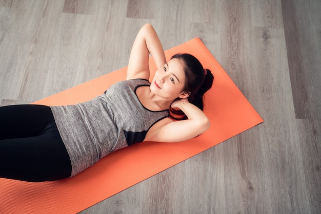 Aziatische vrouw die sportkleding draagt die sit-up op oranje mat in woonkamer doet