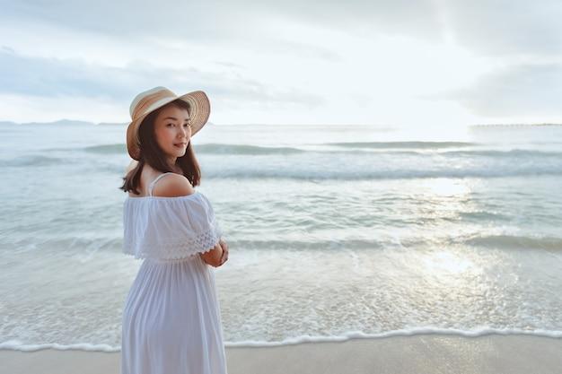 Aziatische vrouw die stijlvolle hoed en kleding draagt die naar de oceaan kijkt en geniet van de prachtige zonsondergang op het strand. zomervakantie en reisconcept
