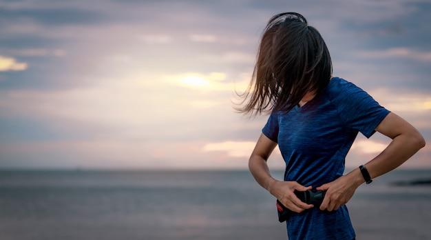 Aziatische vrouw die taillezak draagt alvorens cardiooefening in het ochtend op zee strand met zonsopganghemel in werking te stellen. outdoor training. runner en smart band draagbaar apparaat. gezonde levensstijl.