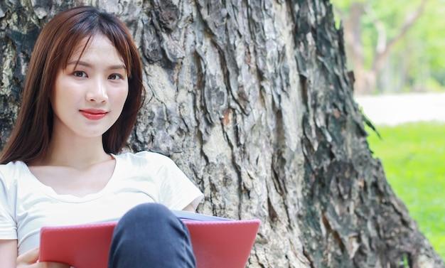 Aziatische vrouw die tegen een boom leunt en een boek leest in het park