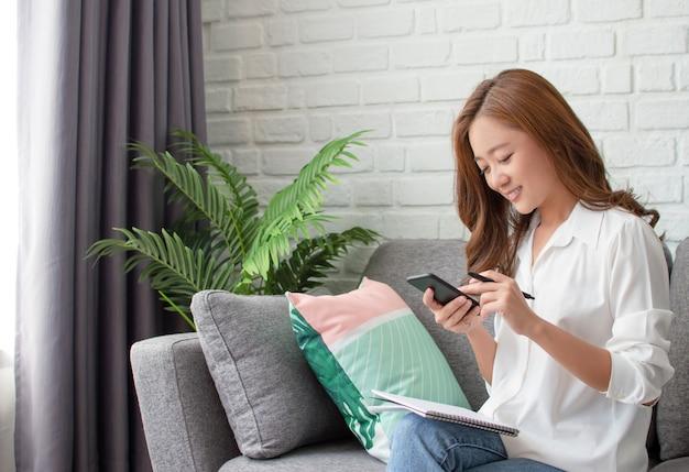 Aziatische vrouw die telefoon gebruikt om mensen te contacteren.