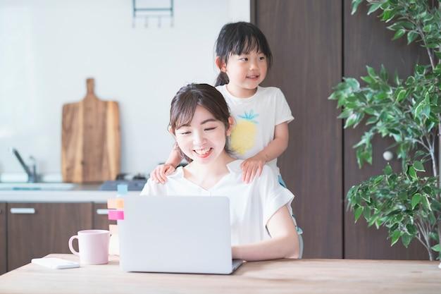 Aziatische vrouw die telework met haar dochter doet