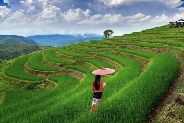 Aziatische vrouw die thaise cultuur traditioneel draagt bij rijstterras van ban pa bong piang in chiang mai, thailand