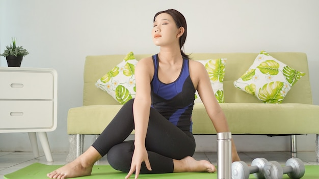 Aziatische vrouw die thuis geniet van haar yogapraktijk