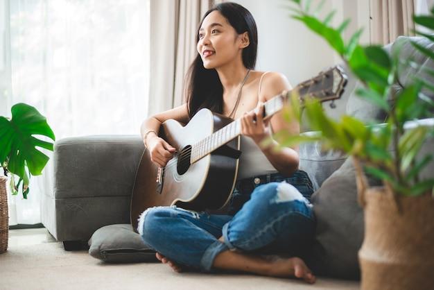 Aziatische vrouw die thuis muziek speelt met gitaar, jonge vrouwelijke gitarist muzikant levensstijl met akoestisch kunstinstrument zit om te spelen en een lied te zingen dat geluid maakt in hobby in de huiskamer