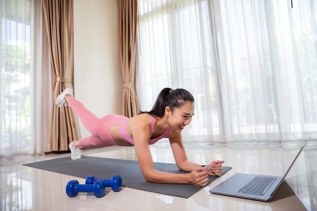 Aziatische vrouw die thuis traint, plank doet en video's op laptop bekijkt