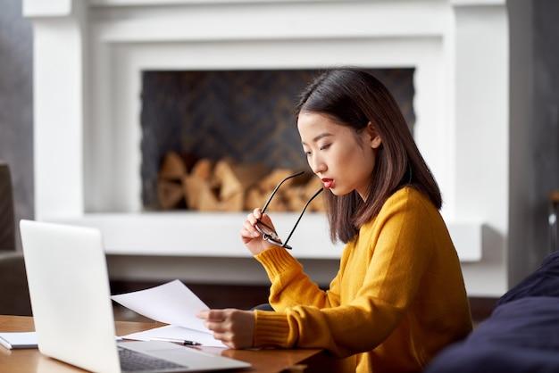Aziatische vrouw die thuis werkt en documenten bekijkt. mooie japanse vrouw