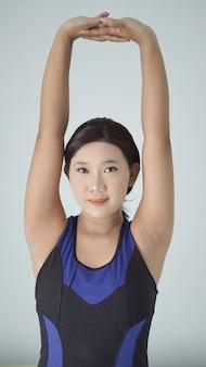Aziatische vrouw die thuis yoga beoefent en handbewegingen opwarmt