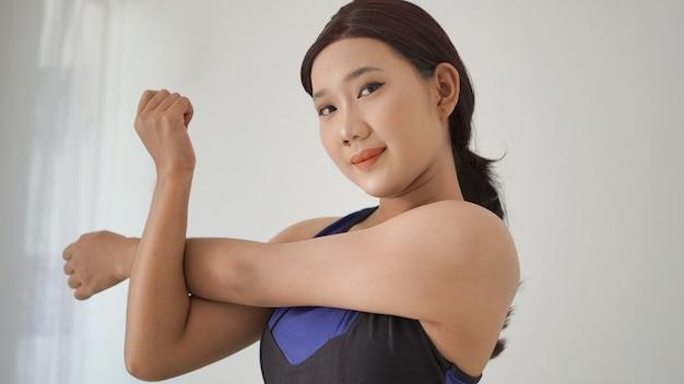 Aziatische vrouw die thuis yoga beoefent en handgebaar opwarmt