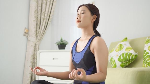 Aziatische vrouw die thuis yoga beoefent met focus