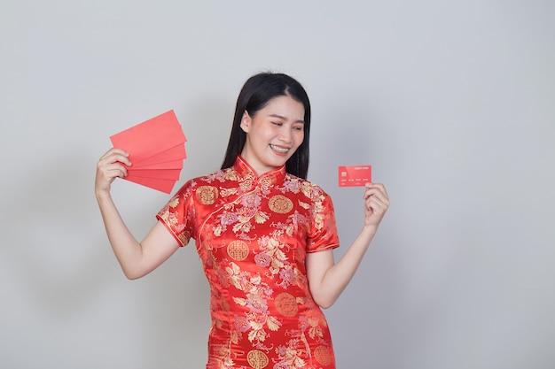 Aziatische vrouw die traditionele cheongsam qipao-jurk draagt met creditcard en rode enveloppen voor chinese nieuwjaarswinkelconcepten.