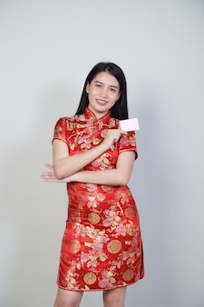 Aziatische vrouw die traditionele cheongsam qipao-kleding draagt die creditcard voor chinese nieuwe jaarwinkelconcepten toont.