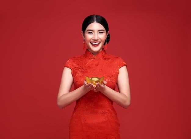 Aziatische vrouw die traditionele cheongsam qipao-kleding draagt die goudstaaf houdt die op rode muur wordt geïsoleerd.