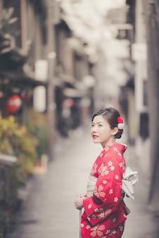 Aziatische vrouw die traditionele japanse kimono draagt die in de oude stad van kyoto loopt