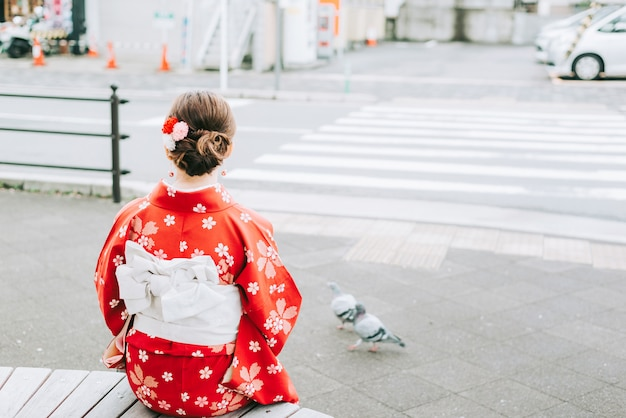 Aziatische vrouw die traditionele japanse kimono ontspannende zitting draagt onder de boom kyoto, ervaart de cultuur van japan