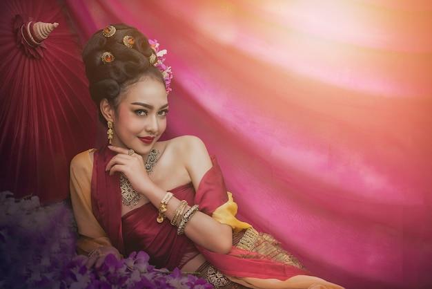 Aziatische vrouw die typische thaise kleding, de uitstekende originele kleding van thailand draagt