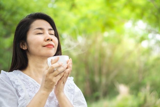 Aziatische vrouw die van hete koffiekop geniet