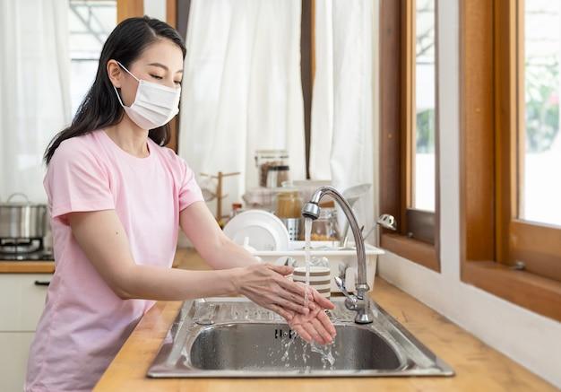 Aziatische vrouw die vanuit huis werkt met een beschermend masker of gezichtsmasker en haar handen wast met schoon water in de keuken thuis tijdens de coronaviruscrisis of covid-19-uitbraak.
