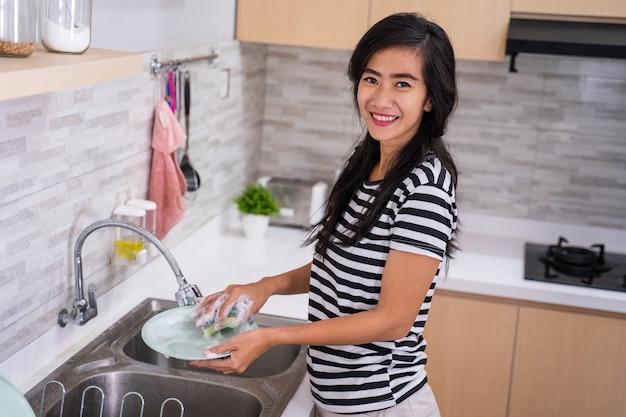 Aziatische vrouw die wat schotel het schoonmaken doet