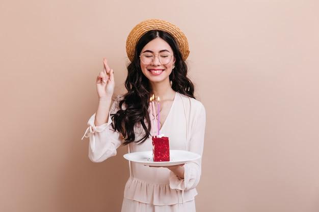 Aziatische vrouw die wens met gesloten ogen maakt. charmante koreaanse vrouw met cake met kaarsen.