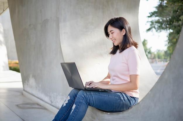 Aziatische vrouw die werk door notitieboekje controleert