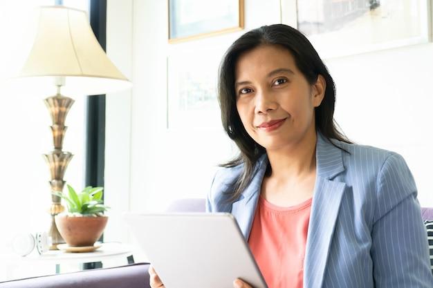 Aziatische vrouw die werkt in kantoor, gelukkige drukke dag
