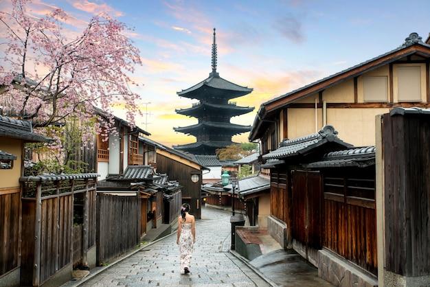 Aziatische vrouw die yasaka in straat dichtbij pagode in de ochtend lopen, kyoto, japan