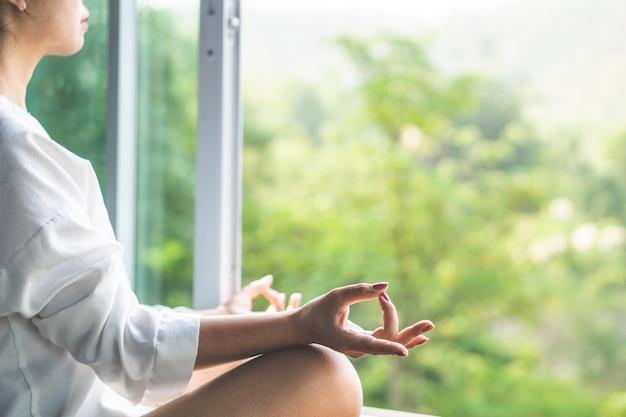 Aziatische vrouw die yoga doet en met aard mediteert