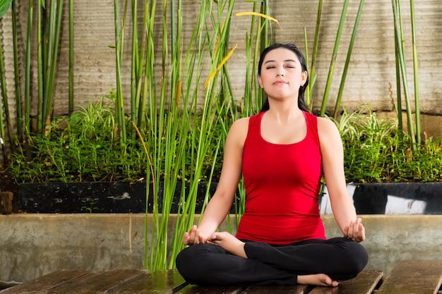 Aziatische vrouw die yoga in het tropische plaatsen doet