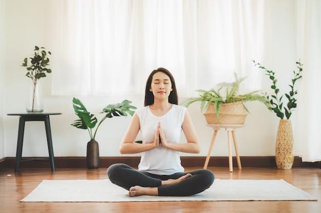Aziatische vrouw die yogameditatie thuis doet