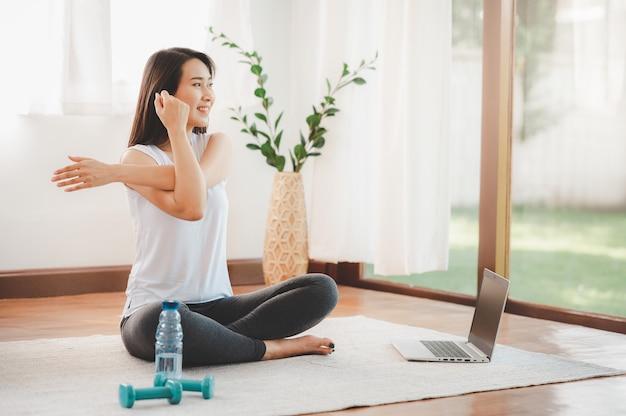 Aziatische vrouw die yogaschouder doet die online klasse thuis uitrekt