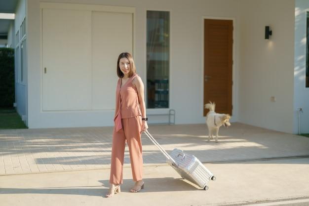 Aziatische vrouw die zich in een nieuw huis beweegt. trek bagage en loop naar de ingang van de huisdeur.