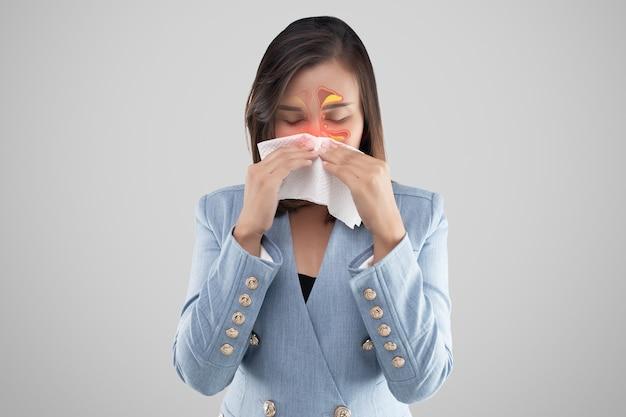 Aziatische vrouw die zich onwel voelt vanwege sinus-symptomen op een grijze achtergrond.
