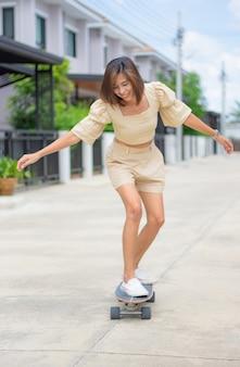 Aziatische vrouw die zich op surfskate bevindt achtergrond van straten en huizen.