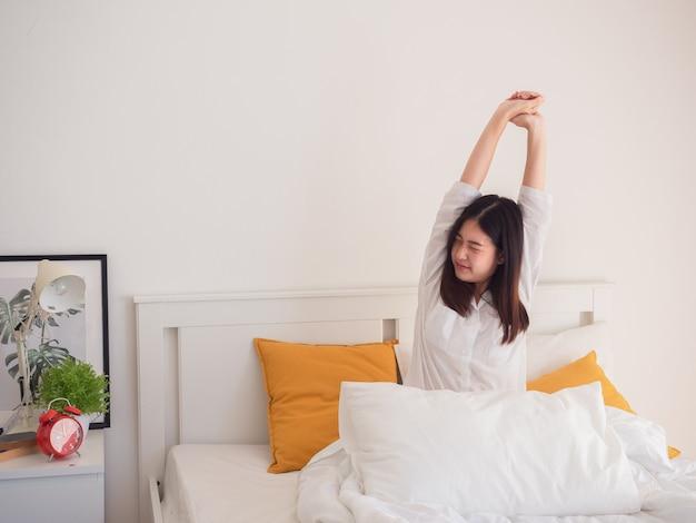 Aziatische vrouw die zich uitstrekt in bed na wakker worden