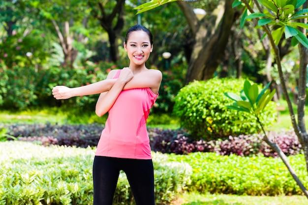Aziatische vrouw die zich uitstrekt spieren voor fitness in stadspark
