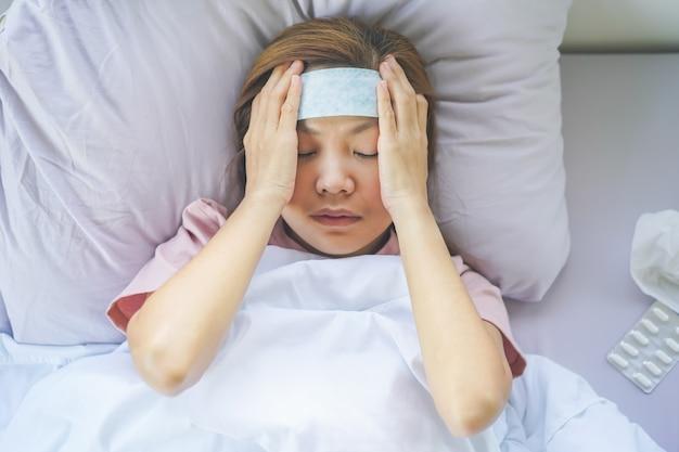 Aziatische vrouw die ziek ligt met behulp van een koortsverlagingsmiddel op het voorhoofd