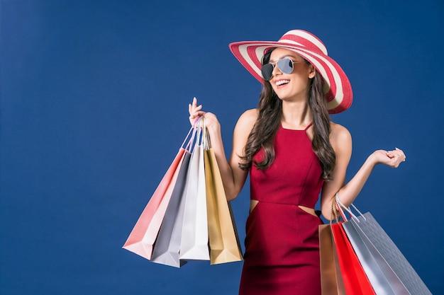 Aziatische vrouw die zonnebril draagt en multi kleuren het winkelen zakken draagt op blauwe kleurenachtergrond