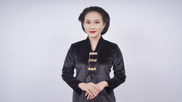 Aziatische vrouw die zwarte kebaya draagt, ziet er elegant uit geïsoleerd op een witte achtergrond