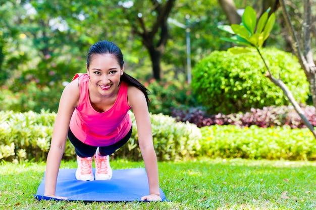 Aziatische vrouw doet push-ups in park