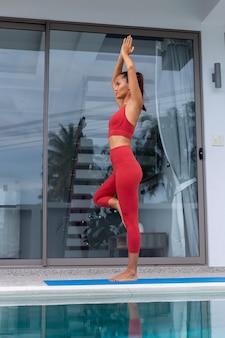 Aziatische vrouw doet yoga buiten villa bij zwembad vrouw in rode sportkleding doet yoga houdingen op de mat