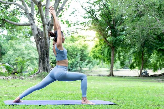 Aziatische vrouw doet yoga in een elegante houding, in het groene park
