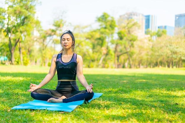Aziatische vrouw doet yoga oefening en ontspannen met sportkleding in groen park in de zomer
