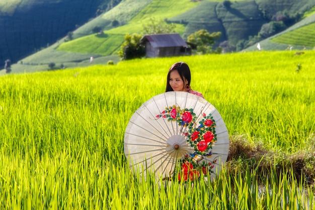 Aziatische vrouw draag traditionele kostuum zitten in terras rijst boerderij