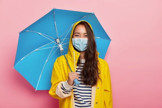 Aziatische vrouw draagt beschermend masker, wordt geconfronteerd met luchtvervuiling tijdens regenachtige dagen, staat onder paraplu, gekleed in gele regenjas