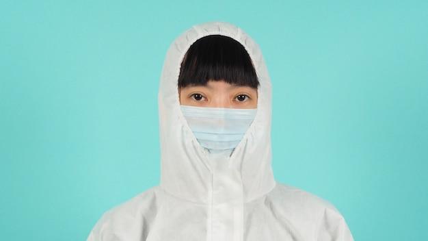 Aziatische vrouw draagt een gezichtsmasker en een ppe-pak op een mintgroene of tiffany blue-achtergrond.