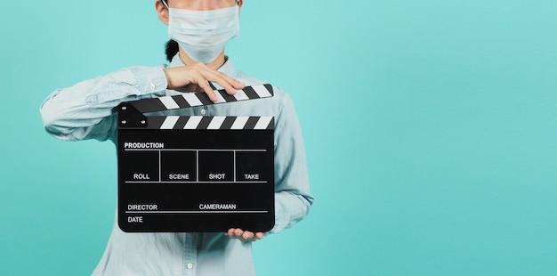 Aziatische vrouw draagt een gezichtsmasker en houdt een zwart klepelbord vast of gebruikt filmleien in videoproductie, bioscoopindustrie op groene munt of tiffany blue achtergrond.
